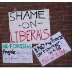 Signs taped to the wall outside the office of Sudbury Liberal MPP Rick Bartolucci during the Solidarity Against Austerity action in Sudbury, Ontario on April 12, 2013