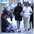 Pedestrians pass a homeless person in front of the Design Exchange on Bay Street in downtown Toronto