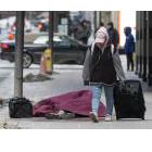 Homeless person under a blanket on a sidewalk in Toronto