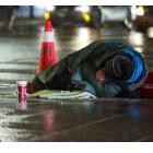 Homeless person in a sleeping bag on a wet sidewalk
