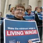 Dozens met on the steps of the Manitoba Legislature to rally for an increase to the province's minimum wage on Tuesday
