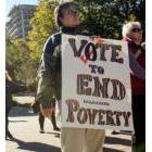 Demonstrator with a poster: Vote to End Legislated Poverty