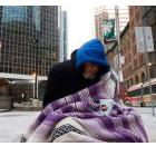 A homeless person panhandles for money during an extreme cold weather alert for the City of Toronto on Dec. 13, 2010