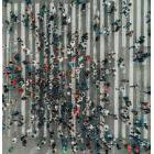Aerial view of a dense crowd of people crossing the street at a major crosswalk.