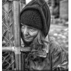 Homeless person standing near a fence