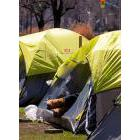 A homeless person lies in a tent pitched in a centre reservation in downtown in Toronto