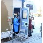 A health-care worker finishes up after a client had a curbside COVID-19 test at Anishnawbe Health Toronto's Mobile Healing Unit